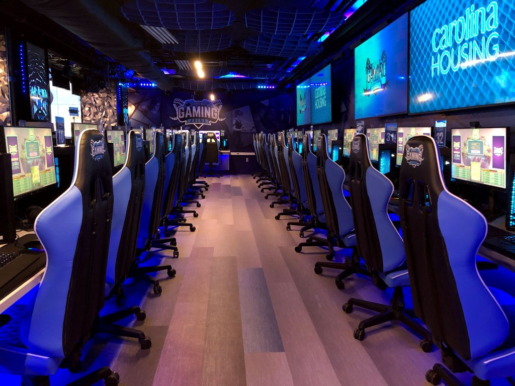 two rows of chairs, computers, monitors and video screens in gaming arena