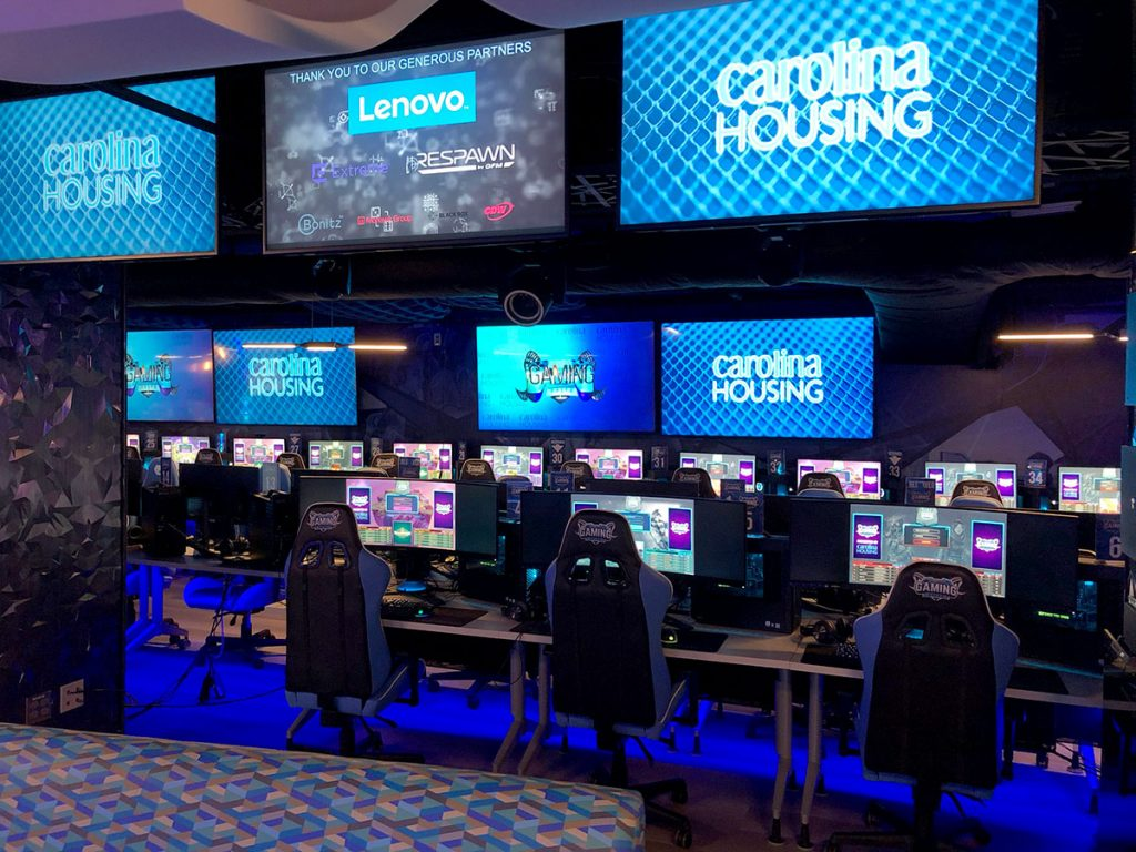 gaming PCs and chairs, with televisions overhead